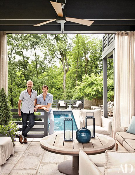 Shea (left) and Booth in the pool lounge, where a pair of Lee Industries armchairs slipcovered in a Sunbrella canvas join a teak-top table by Terry Hunziker for Sutherland; the lanterns are by RH.
