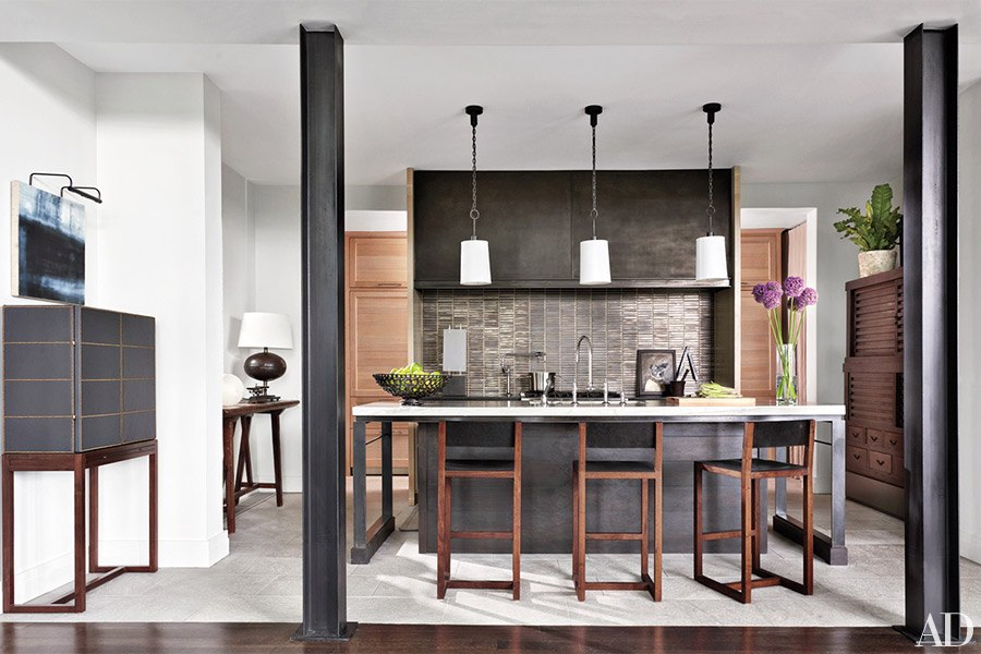 In the kitchen, Roman Thomas pendant lights are installed above the Ray Booth–designed island, Ann Sacks tile was used for the backsplash, the sink fittings are by Kohler, and the stools are by BDDW; a painting by Louise Crandell surmounts the bar cabinet, at left, which was devised by Booth and is clad in an Edelman leather.