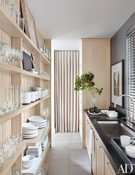 The working pantry, lined with open shelves for tableware, has a Kohler sink and fittings.